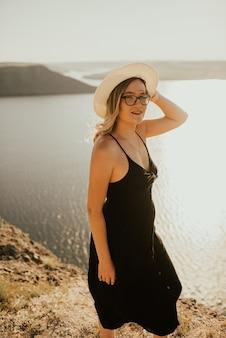 Jonge vrouw jurk met een hoed en bril staat op een klif boven zee bij zonsondergang.