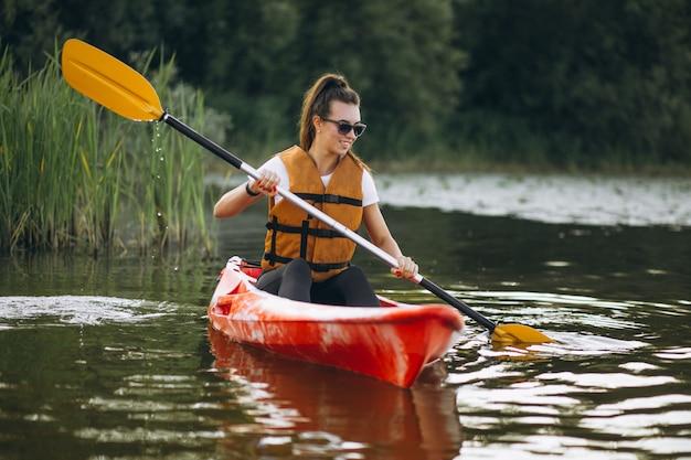Jonge vrouw kajakken op het meer