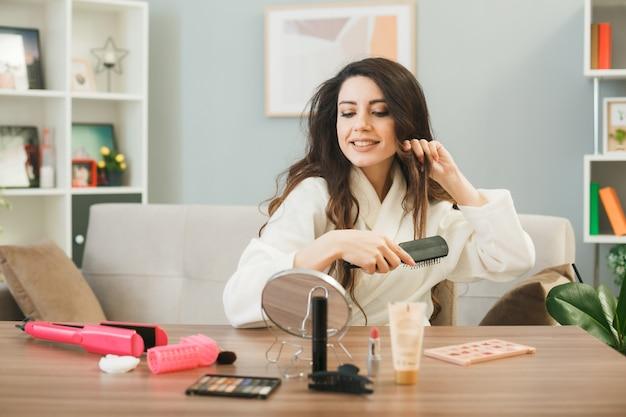 Jonge vrouw kamt haar zittend aan tafel met make-up tools in de woonkamer