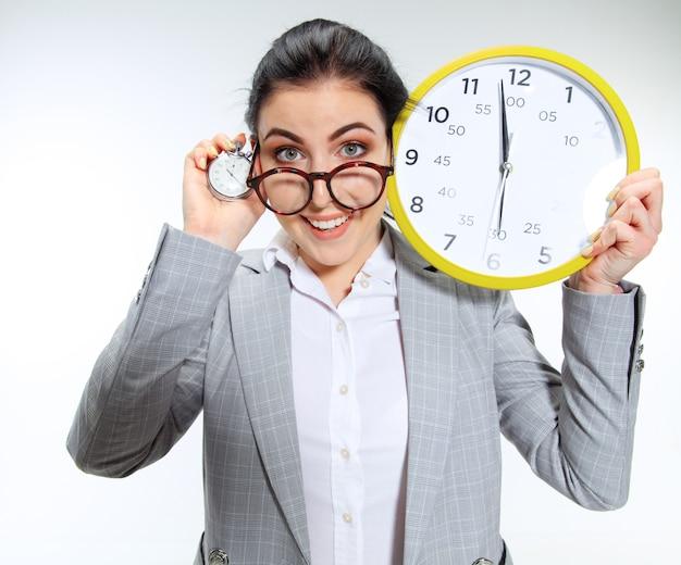 Jonge vrouw kan niet wachten om van het vervelende kantoor naar huis te gaan. de klok vasthouden en vijf minuten voor het einde wachten. concept van de problemen, zaken of problemen van de beambte met geestelijke gezondheid.