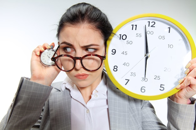 Jonge vrouw kan niet wachten om van het vervelende kantoor naar huis te gaan. de klok vasthouden en vijf minuten voor het einde wachten.