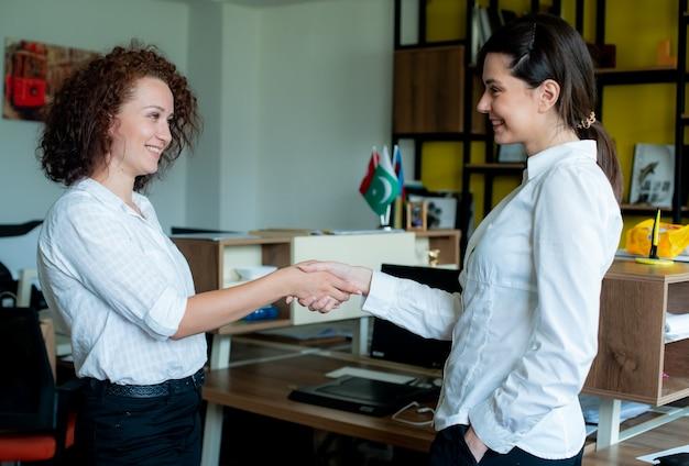 Jonge vrouw kantoormedewerker glimlachend vriendelijk handen schudden met collega staande op kantoor