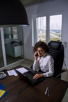 Jonge vrouw kantoormedewerker met bril spreekt aan de telefoon met klanten contactcenter