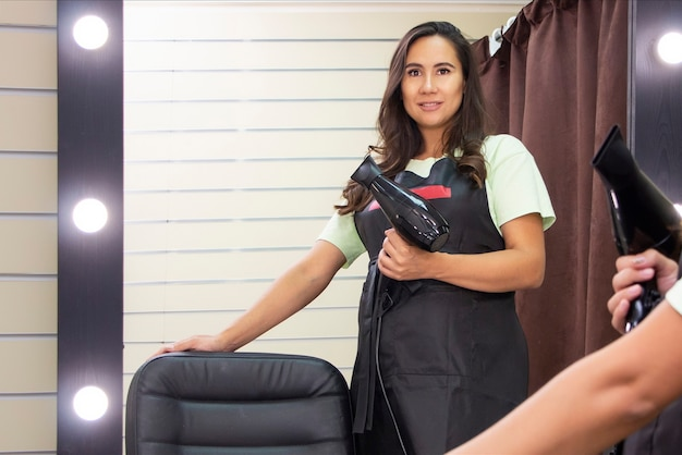 Jonge vrouw kapper met een haardroger in haar handen nodigt uit naar een schoonheidssalon.