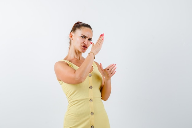 Jonge vrouw karate hakken gebaar in gele jurk tonen en hatelijk, vooraanzicht kijken.