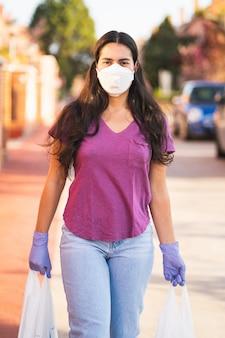 Jonge vrouw keert terug van winkelen met tassen in handen met medische handschoenen en een virusmasker tijdens de coronavirus pandemie in de straat