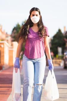 Jonge vrouw keert terug van winkelen met tassen in handen met medische handschoenen en virusmasker tijdens het coronavirus in de straat