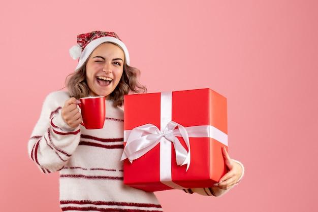 Jonge vrouw kerst aanwezig en kopje thee op roze te houden