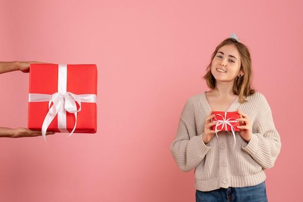 Jonge vrouw kerst aanwezig houden en het accepteren van geschenk van man op roze