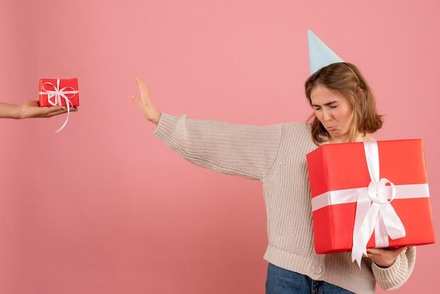 Jonge vrouw kerst aanwezig te houden en geschenk van man op roze te verwerpen