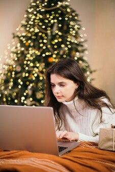 Jonge vrouw kerst online winkelen zittend op het bed