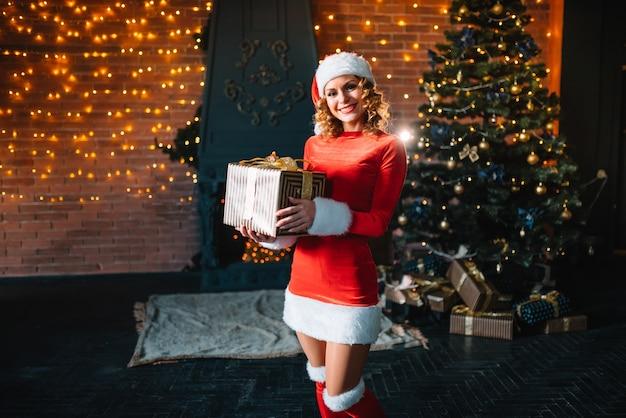 Jonge vrouw kerstcadeautjes uitpakken in de buurt van verlichte boom. kerstmis, nieuwjaar viering concept.