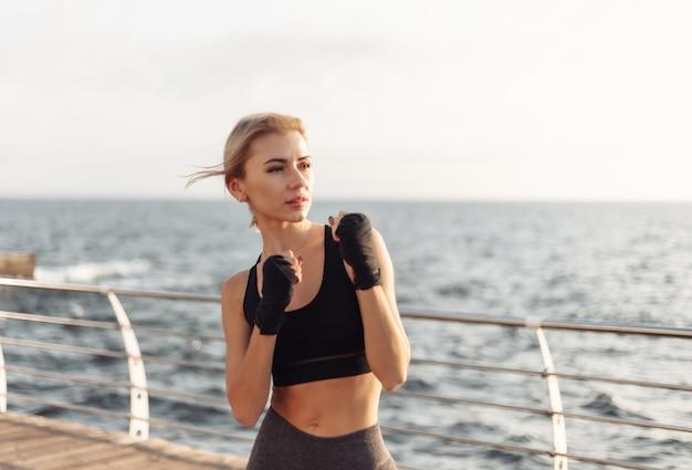 Jonge vrouw kickbokser in sportwear met ingepakte handen in verbandtreinen op het strand bij zonsopgang
