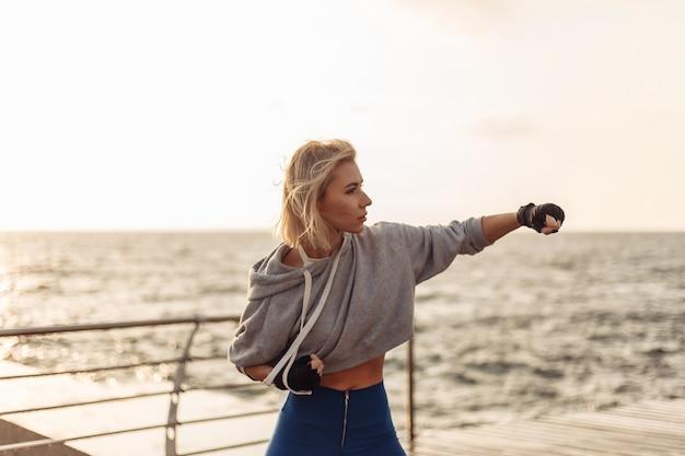 Jonge vrouw kickbokser met gewikkelde handen in pleisters traint een klap op het strand bij zonsopgang