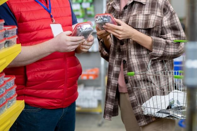 Jonge vrouw kiest nagels in ijzerhandel terwijl winkelbediende haar helpt