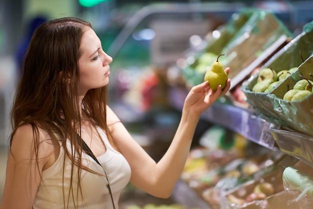 Jonge vrouw kiest peren in de winkel