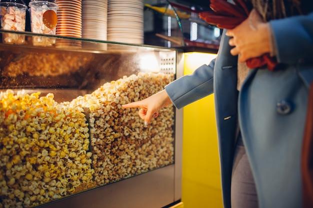 Jonge vrouw kiest popcorn in de bioscoop
