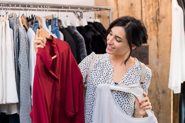 Jonge vrouw kiezen tussen jurken in kledingwinkel