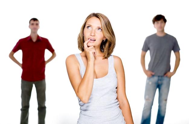 Jonge vrouw kiezen uit twee jonge mannen op wit wordt geïsoleerd
