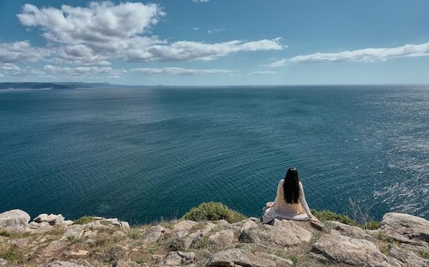 Jonge vrouw kijken naar de zee op een zonnige dag met wolken aan de hemel vanaf de top van een klif