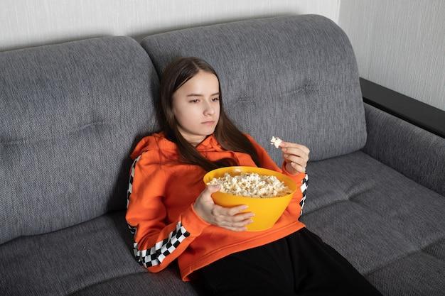 Jonge vrouw kijken naar een oninteressante show op tv met popcorn in haar handen