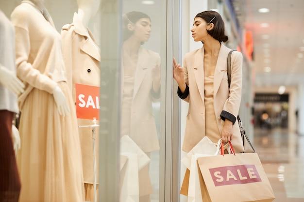 Jonge vrouw kijken naar etalages in boutique