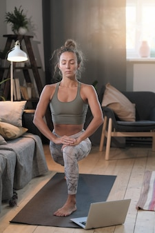 Jonge vrouw kijken naar sport training online op laptop en thuis oefenen