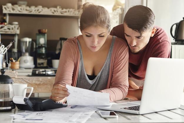 Jonge vrouw kijken naar stuk papier met een serieuze blik, zittend aan de keukentafel met laptop, rekenmachine en documenten