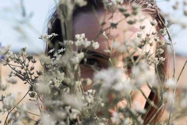 Jonge vrouw kijkt door een boeket van wilde bloemen op het veld.