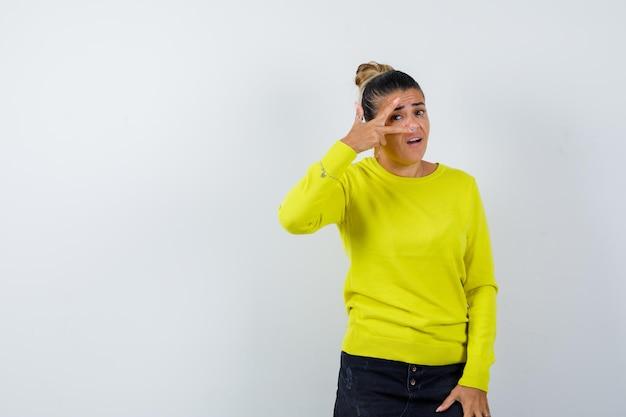 Jonge vrouw kijkt door vingers in trui, spijkerrok en ziet er zelfverzekerd uit