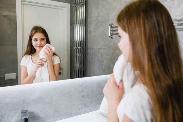 Jonge vrouw kijkt in de badkamerspiegel, raak schoon geen make-upgezicht aan met witte handdoek, ritueel voor huishygiëne. een lachend meisje wordt weerspiegeld in de badkamerspiegel terwijl ze haar handen wast.