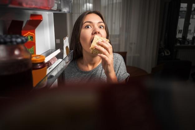 Jonge vrouw kijkt in de koelkast, uitzicht vanuit de koelkast, meisje eet 's nachts, angsten