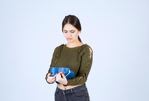 Jonge vrouw kijkt naar blauwe geschenkdoos met boze uitdrukking op witte achtergrond.