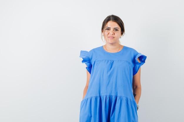 Jonge vrouw kijkt naar camera in blauwe jurk en ziet er verstandig uit