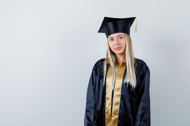Jonge vrouw kijkt naar de camera in afgestudeerd uniform en ziet er verstandig uit.
