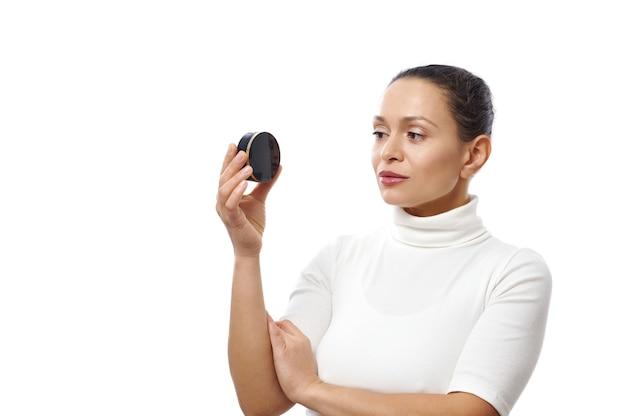 Jonge vrouw kijkt naar een zwarte container in haar hand staande geïsoleerd op een wit oppervlak met kopie ruimte