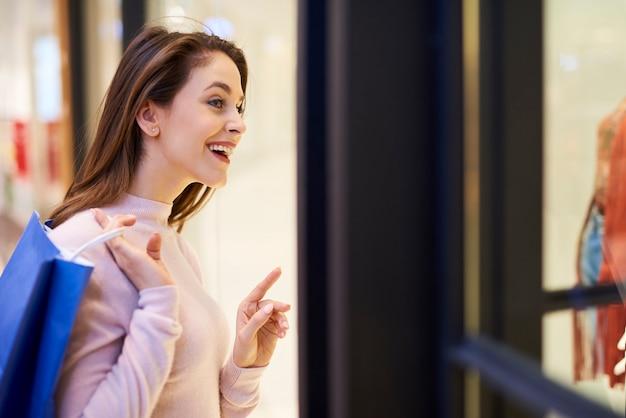 Jonge vrouw kijkt naar etalage met kleding