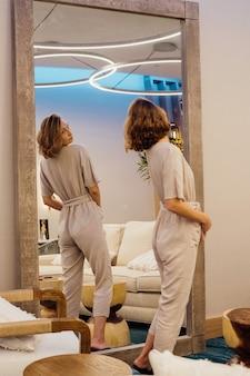 Jonge vrouw kijkt naar haar spiegelbeeld in de grote spiegel