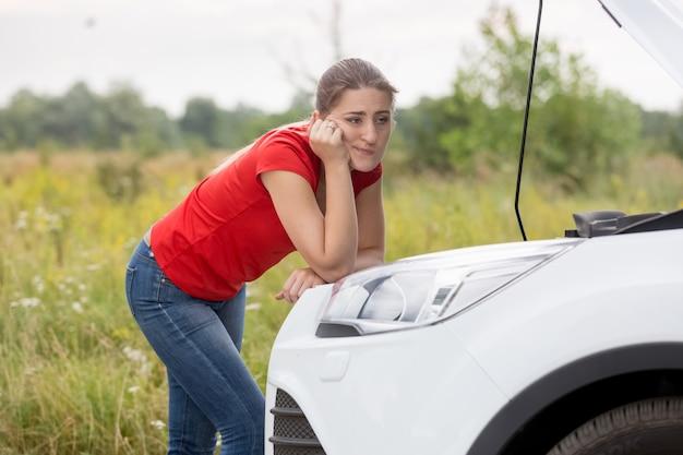 Jonge vrouw kijkt naar kapotte automotor op landelijke weg