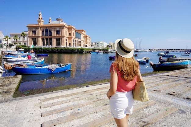 Jonge vrouw kijkt naar margherita theater en vissersboten in de oude haven van bari, regio apulië, italië,