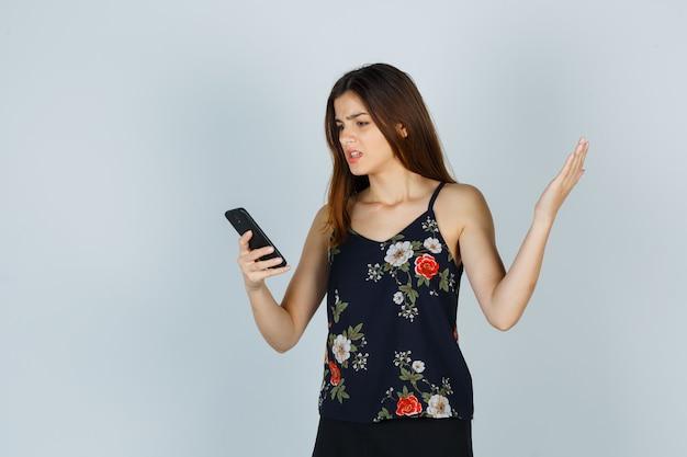Jonge vrouw kijkt naar smartphone in blouse, rok en ziet er nerveus uit. vooraanzicht.