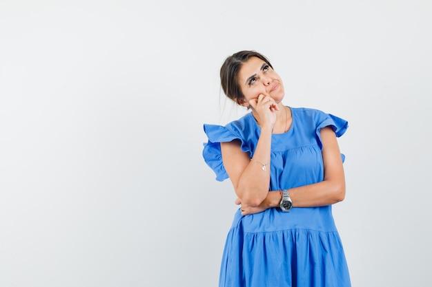 Jonge vrouw kijkt omhoog in blauwe jurk en kijkt peinzend