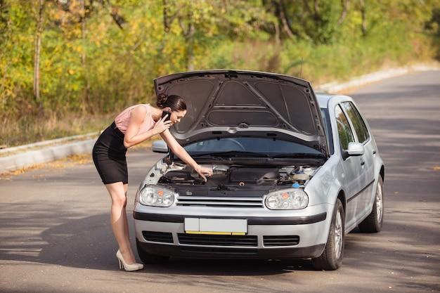 Jonge vrouw kijkt onder de motorkap van uw auto en veroorzaakt de evacuatie, omdat haar auto kapot is gegaan