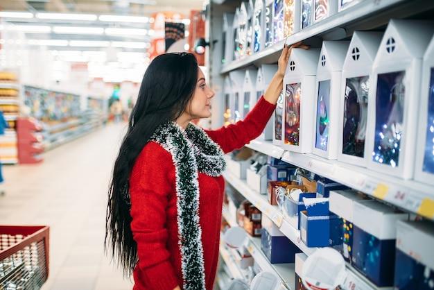 Jonge vrouw kijkt op kerstcadeaus in de supermarkt.