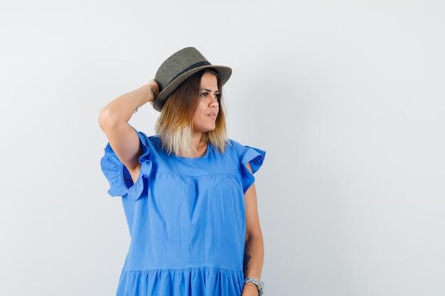 Jonge vrouw kijkt opzij met de hand achter het hoofd in blauwe jurk, hoed en ziet er heerlijk uit