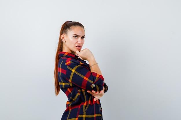Jonge vrouw kijkt over de schouder terwijl ze poseert in crop top, geruit hemd, broek en ziet er charmant uit. vooraanzicht.