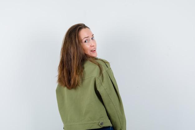 Jonge vrouw kijkt over schouder in overhemd en ziet er charmant uit. achteraanzicht.