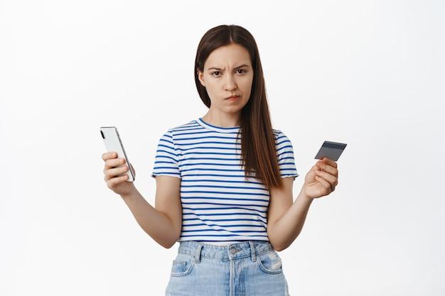 Jonge vrouw kijkt twijfelachtig, frons wenkbrauwen en staart aarzelend, achterdochtig naar voren, met smartphone met creditcard, concept van online winkelen en geld.