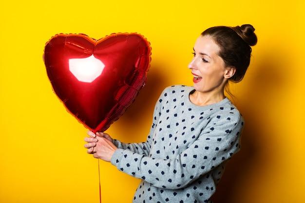 Jonge vrouw kijkt vreugdevol naar een rode luchtballon in de vorm van een hart op een gele achtergrond.