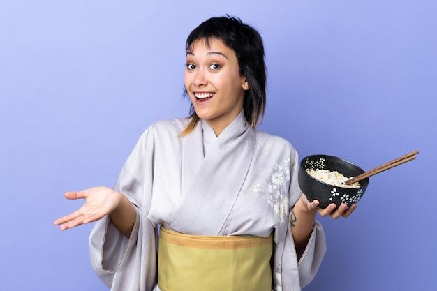 Jonge vrouw kimono dragen over geïsoleerde blauwe muur met geschokte gelaatsuitdrukking terwijl het houden van een kom noedels met stokjes